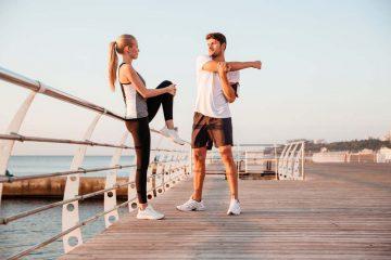 Nainen ja mies venyttelevät meren rannassa kesken lenkin.